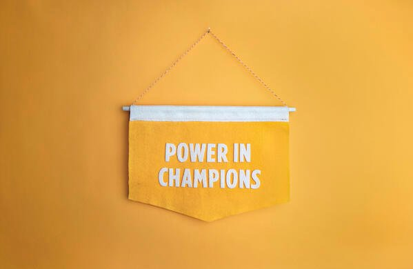 """A yellow banner that says """"power in champions"""""""