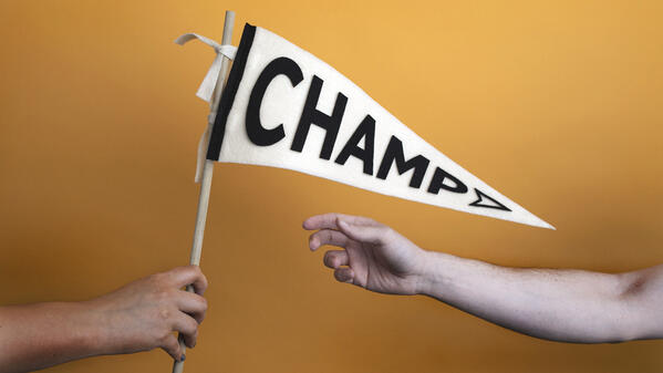 "Image of someone giving a flag to another person. The flag has ""Champ"" written on it."