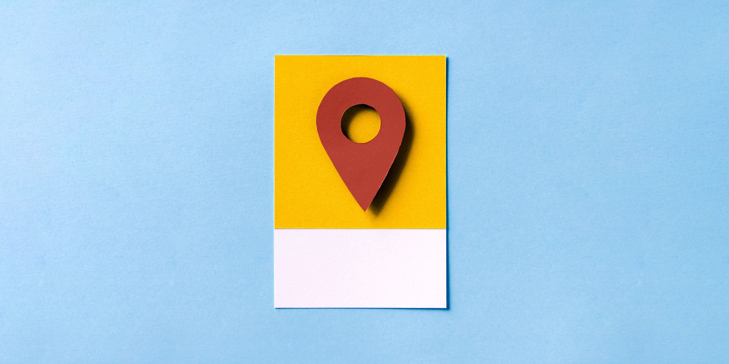 A red pin point symbol on yellow paper.