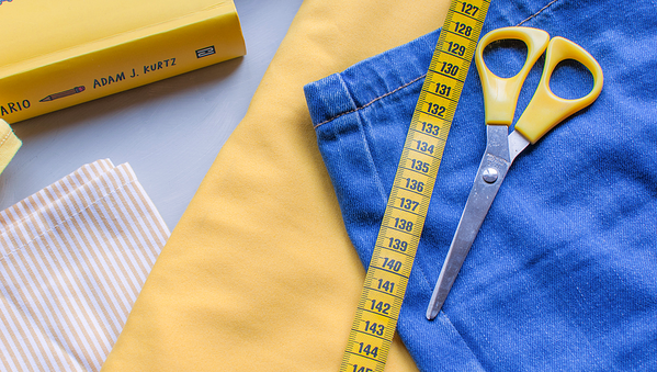Cloth, scissors, and a tape measure on a table