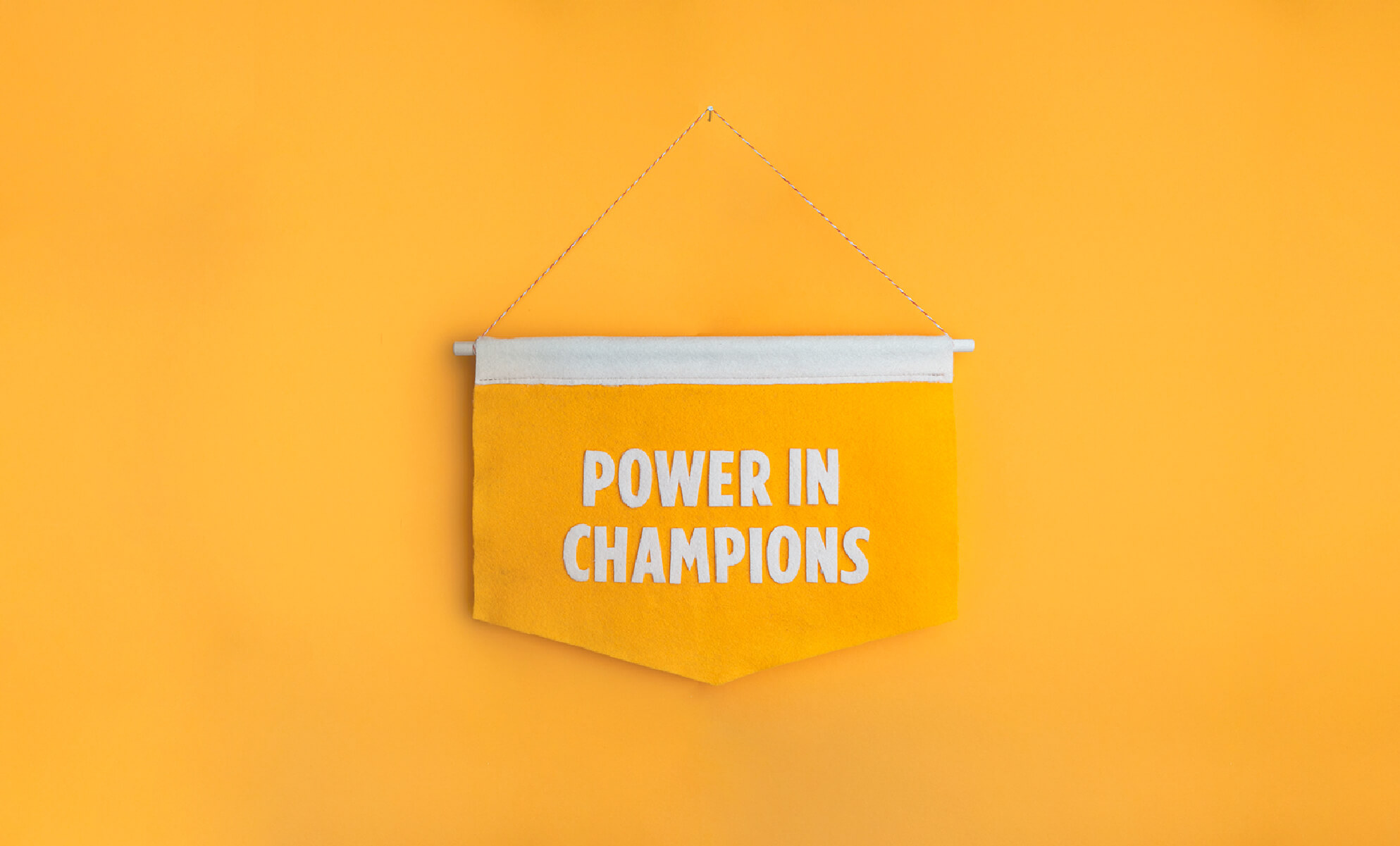 """Yellow felt banner with white felt text, """"Power in champions,"""" against a yellow wall; image by BrainStorm, Inc. 2020@2x-100"""