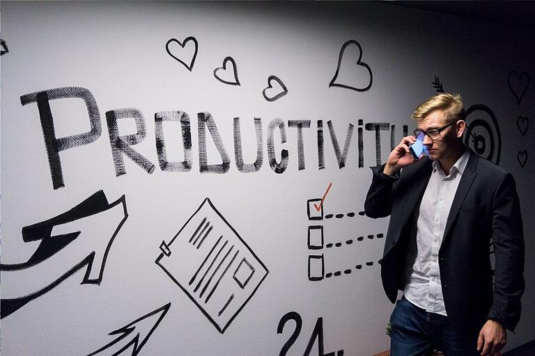 "Andreas Klassen for Unpslash: image of man on mobile phone next to a large whiteboard listing the word ""Productivity"""