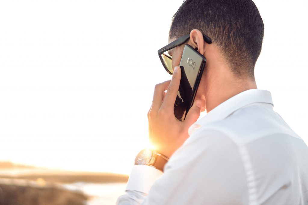 Photo of man talking on a mobile phone while overlooking a nature scene. Image source: Hassan Ouajbir via Unsplash.