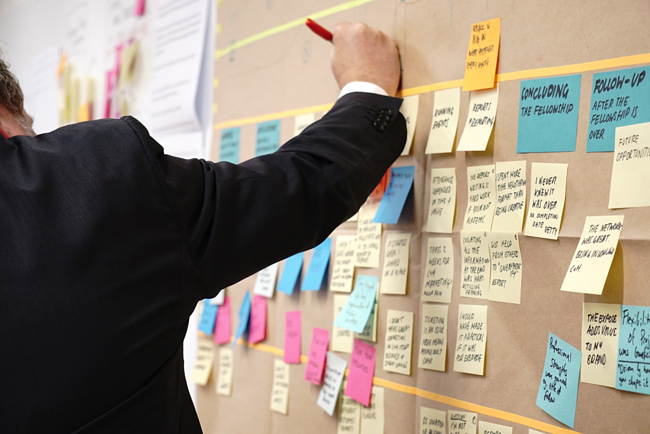 managing a project, man writes on post-it notes on a wall