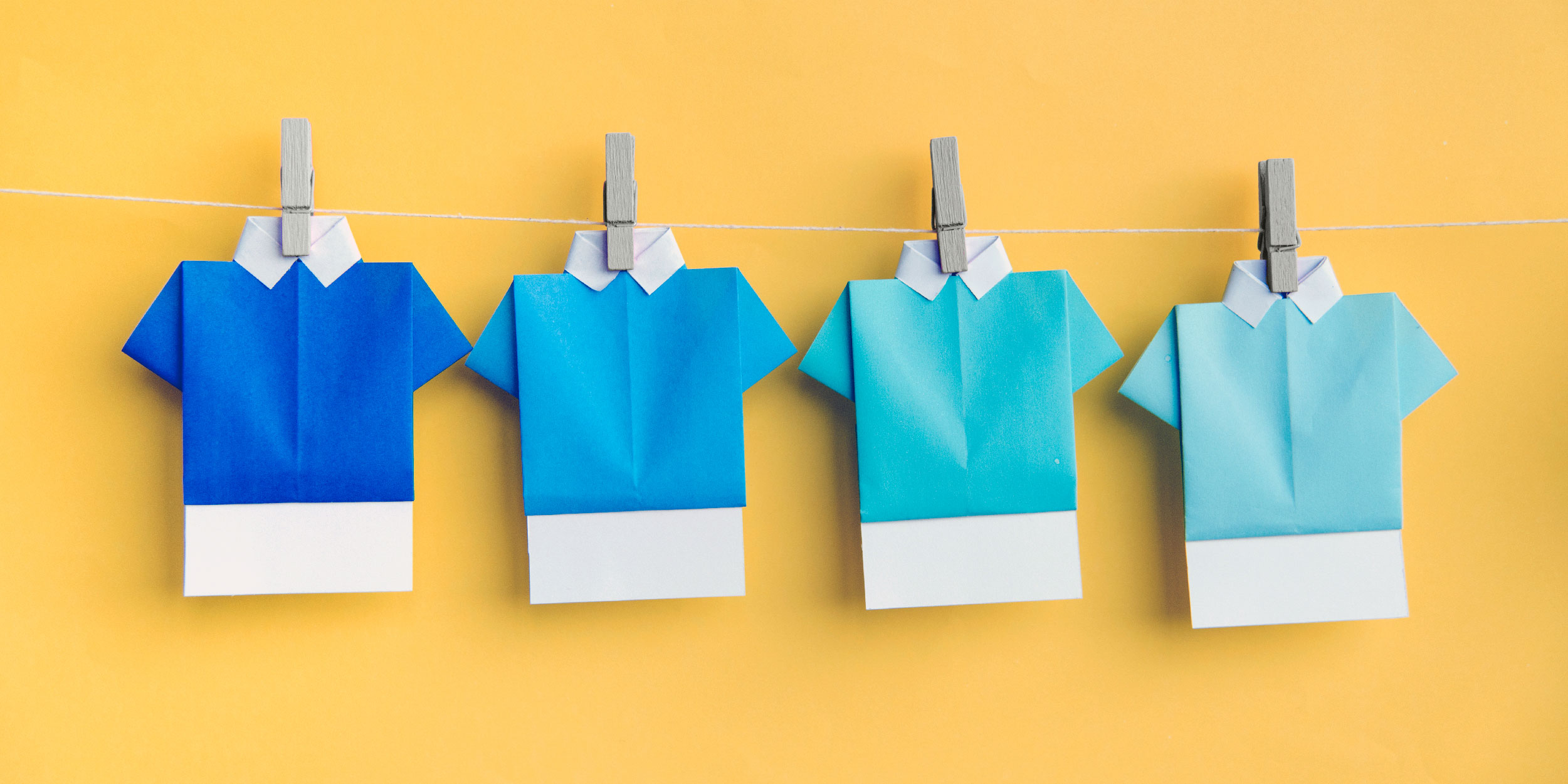 Four blue origami shirts pinned on a clothesline