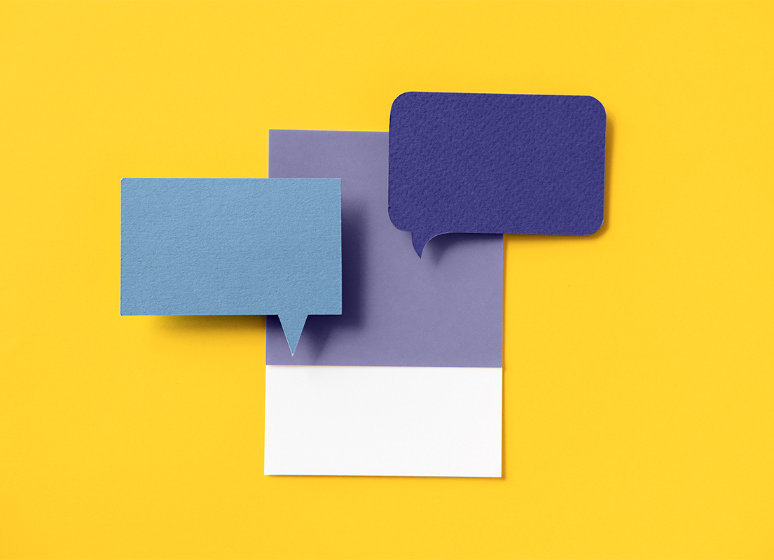 Pieces of blue and purple paper cut into the shape of a chat bubble