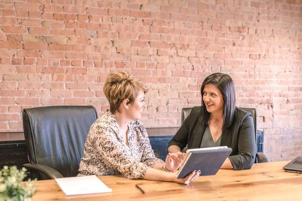 Two women talking in a work setting
