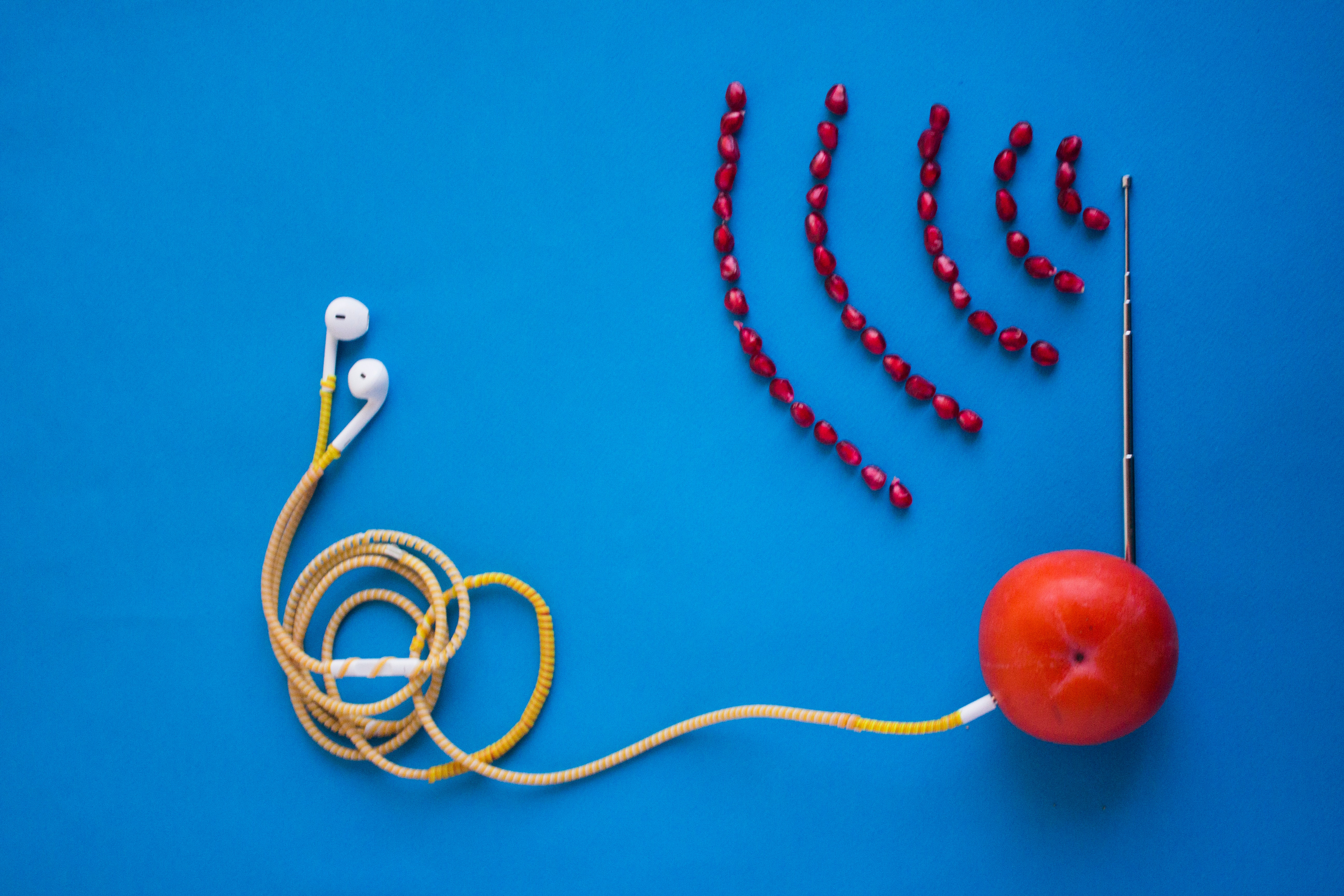 Image of a tomato with earbuds plugged into the tomato on the left side and an antenna sticking up from the top of the tomato with a signal emitting from the antenna made from pomegranate seeds.