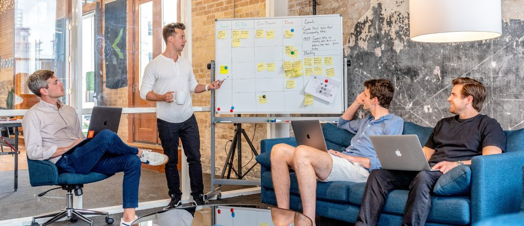 Group of young male business associates gather around a whiteboard. Image by Austin Distil via Unsplash.