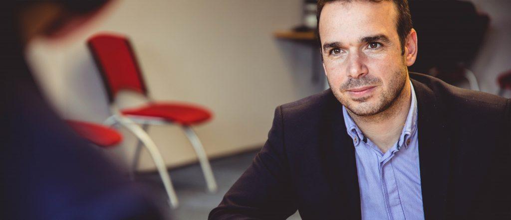 Man engaged in a business conversation, photo by Johanna Buguet via Unsplash.